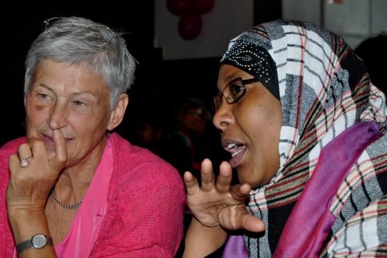 Foto af to kvinder. Den ene er ældre og har lys hud. Den anden er ung og har mørk hud.