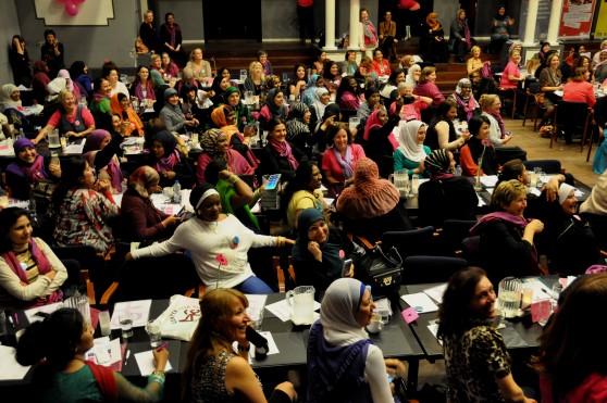 Foto af sal med langborde, hvor mange kvinder er samlet.