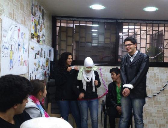 Foto af unge mænd og kvinder med sammenbundne hænder og bind for øjnene. Det er en øvelse. De griner