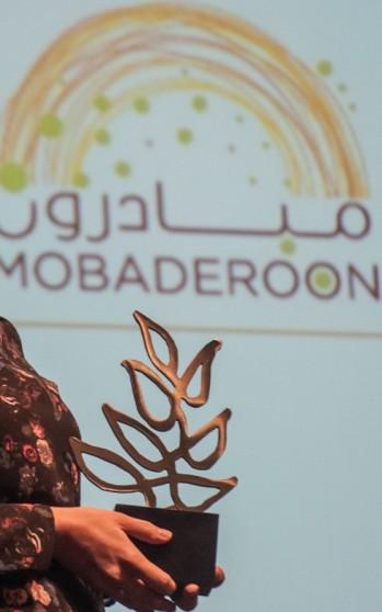 Foto af hænder, der holder prisen. I baggrunden er Mobaderoons logo.